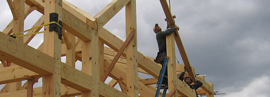 men assembling a timber frame structure