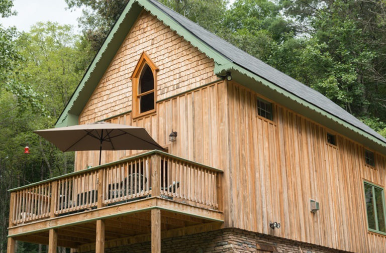 Finished exterior of a timber frame camp with a porch