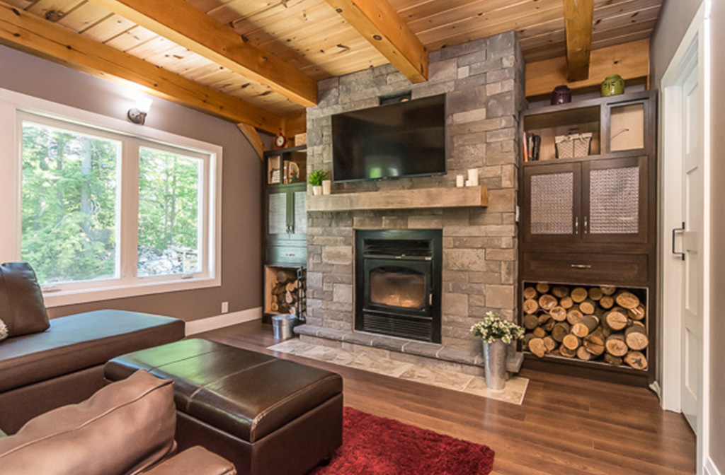 Stone fireplace in the living room of a timber frame dutch saltbox