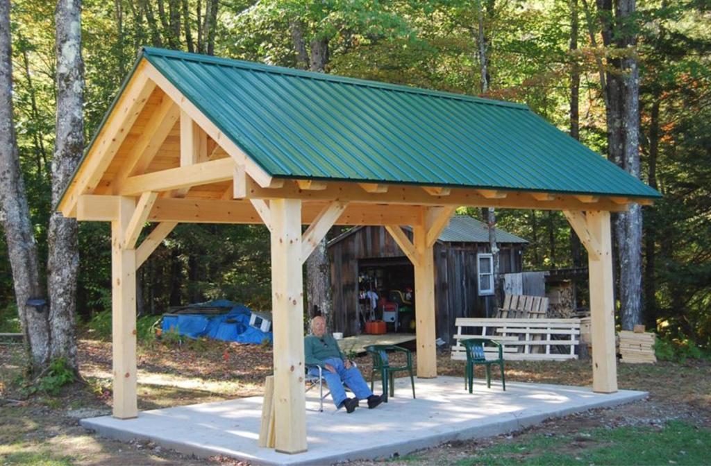 Man sitting under the finished timber frame pavilion