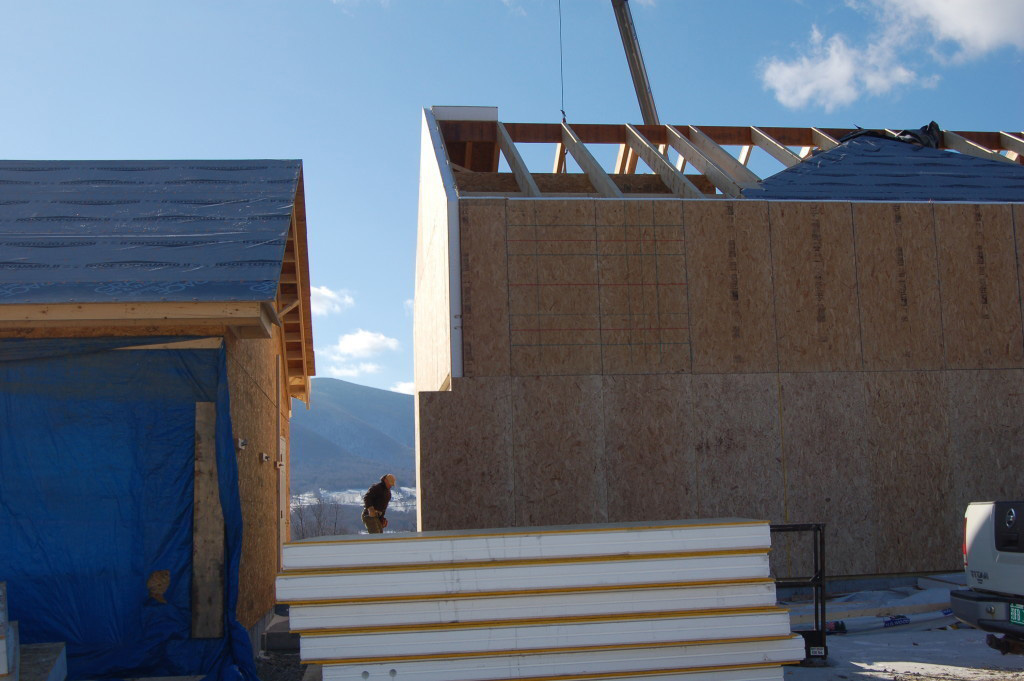Stack of SIPs in front of a timber frame exterior