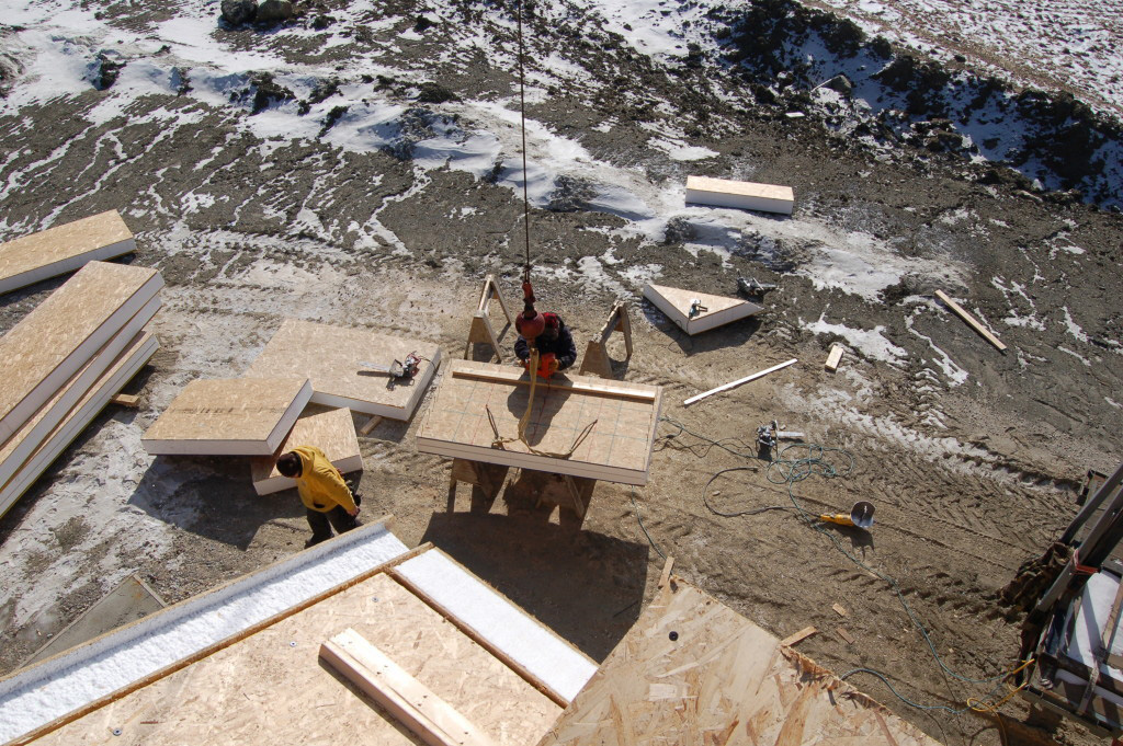 Employees lifting SIPs to be installed on a timber frame