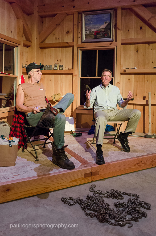 Two people on a stage in the timber frame barn