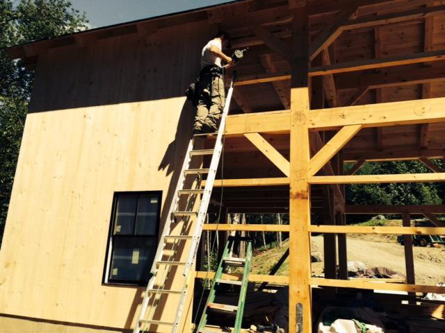 employee working on a timber frame barn