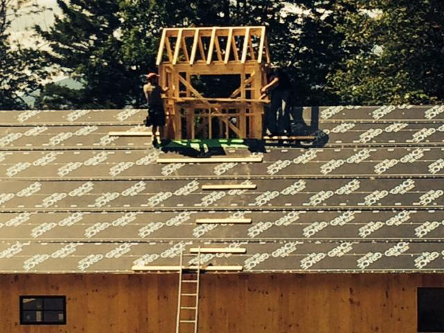 Employees working on a timber frame barn roof