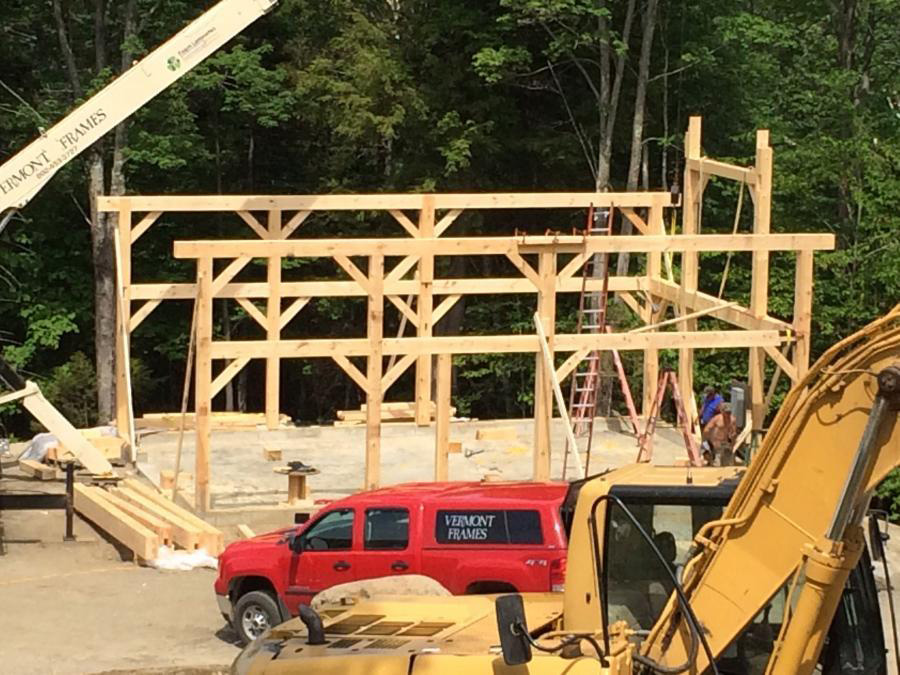 Timber frame beam structure of a barn with a crane and other construction vehicles
