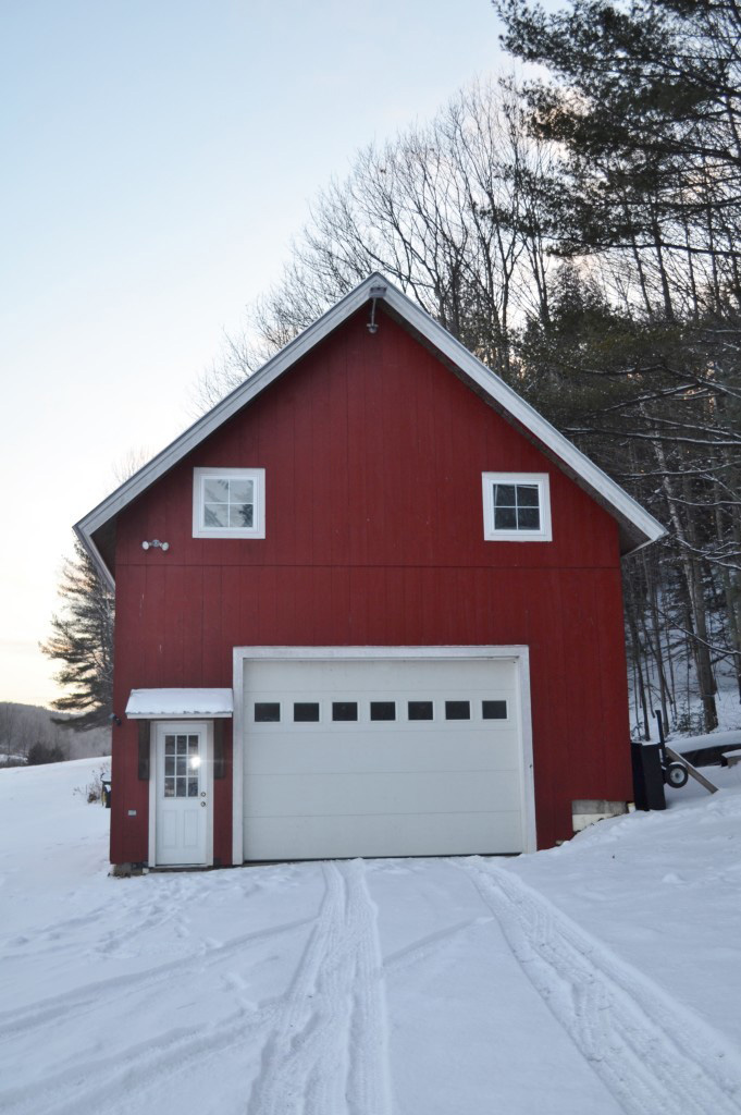 Finished exterior of a red timber frame barn in the winter