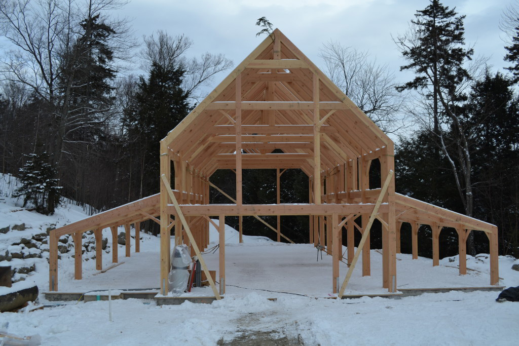 Timber frame structure of a barn in the winter
