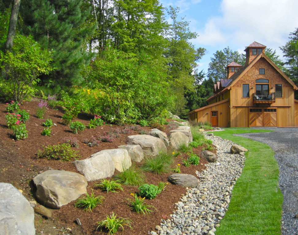 Finished exterior of a timber frame barn with greenery lining the driveway