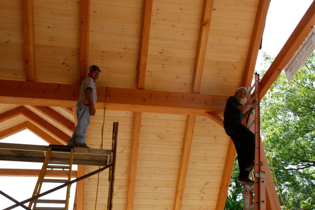 Vermont Frames employees on ladders in a timber frame cape