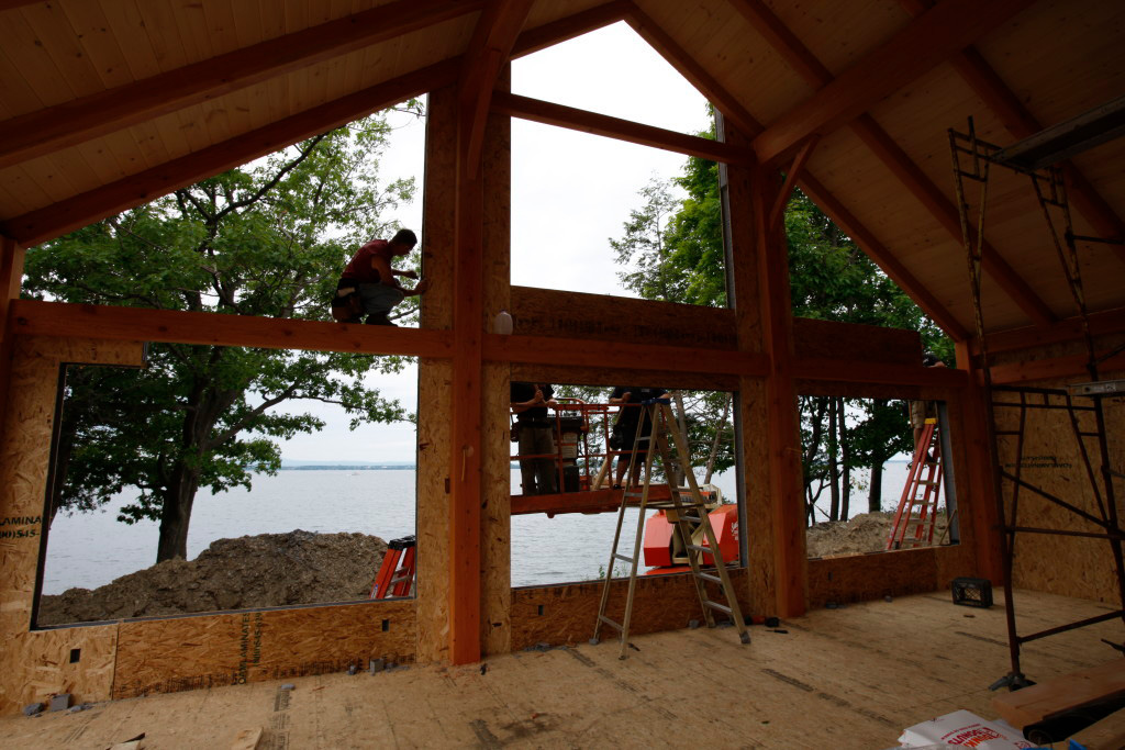 Timber frame cape structure from the inside with employees working