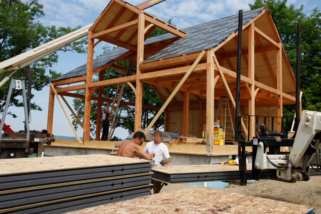 Employees working outside a timber frame cape structure
