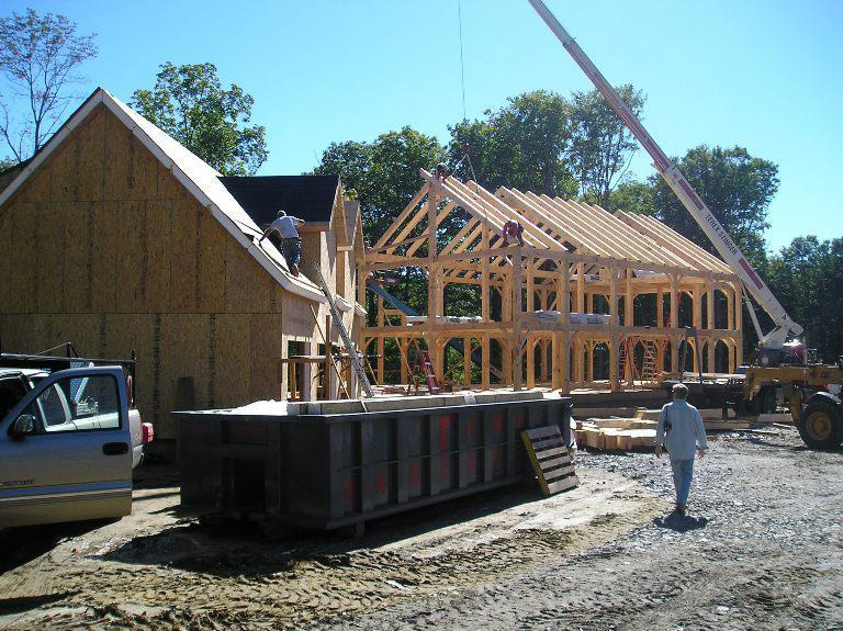 Vermont Frames employee on the roof of a timber frame colonial