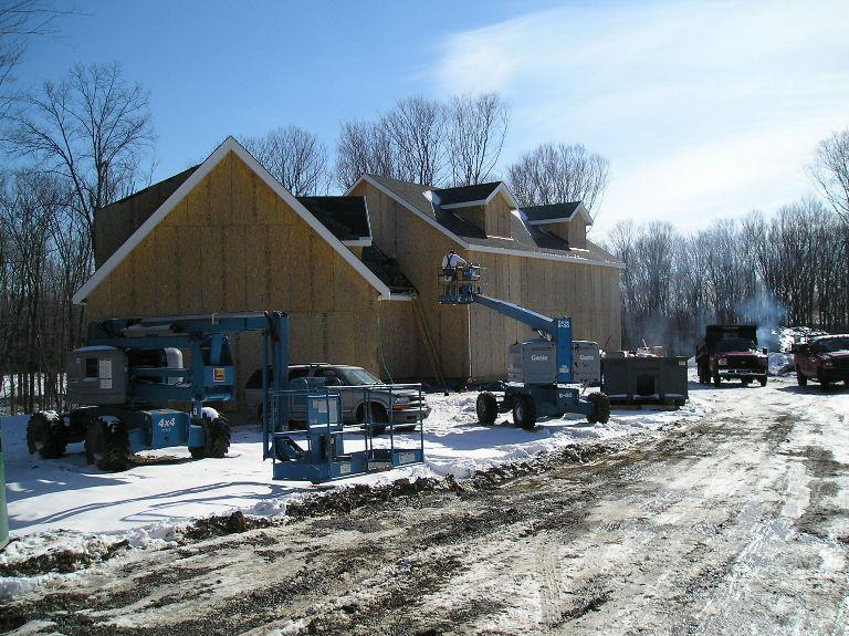 Timber frame structure of a colonial with construction vehicles surrounding it