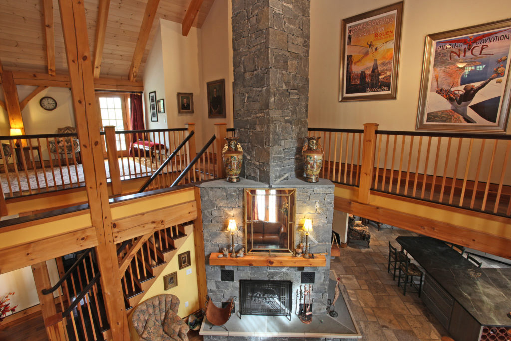 Stone chimney and fireplace in a timber frame colonial