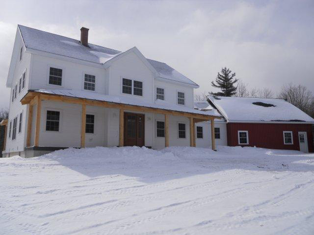 Finished exterior of a timber frame colonial with an attached garage