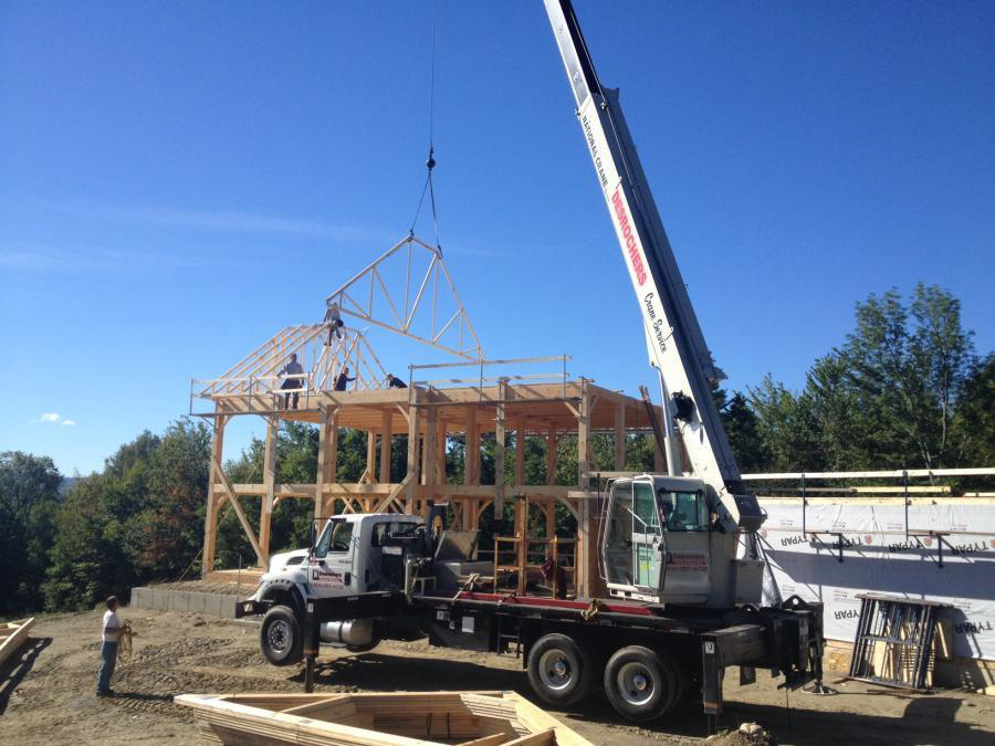 A crane bringing a truss to the top of the colonial frame structure