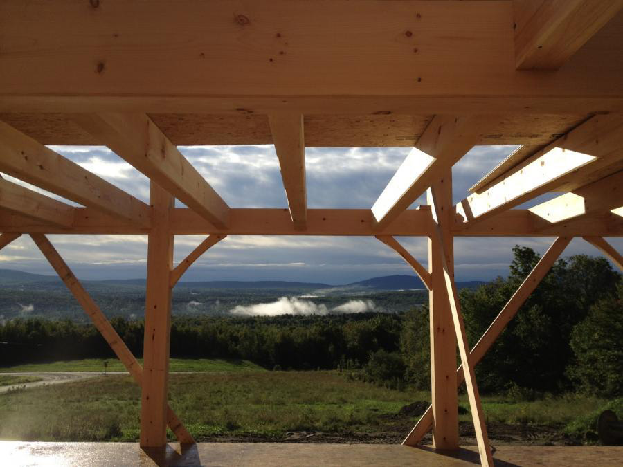 Underneath a timber frame colonial structure looking out at the mountains