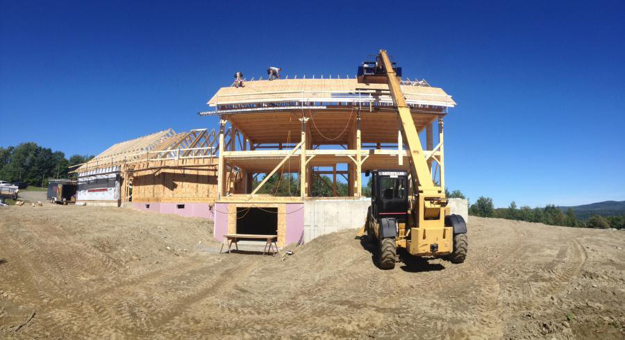 A manlift and employees working on the roof of a timber frame colonial