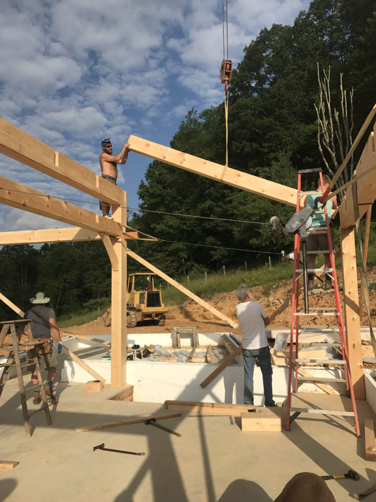 Employees working on a timber frame structure for a contemporary building