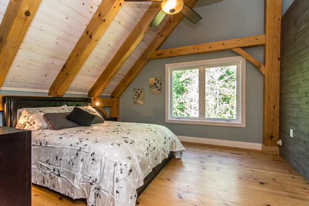 Bedroom with a titled ceiling in a timber frame dutch saltbox