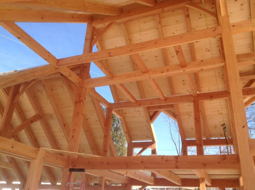 Timber frame dutch saltbox structure with wood panels covering the roof