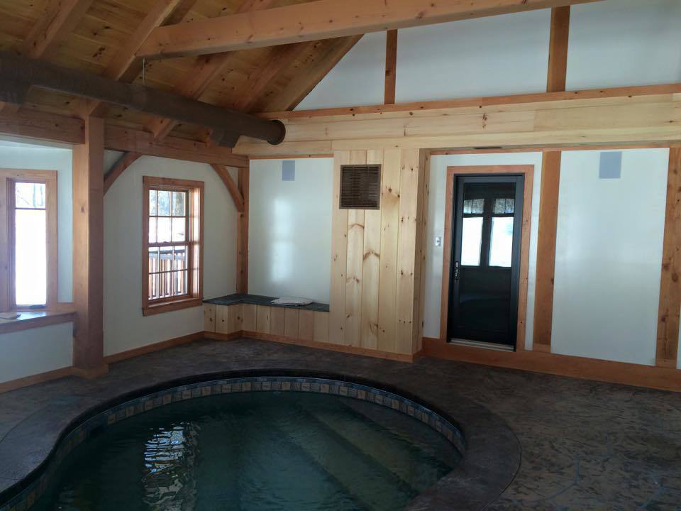 Indoor pool room in a timber frame dutch saltbox