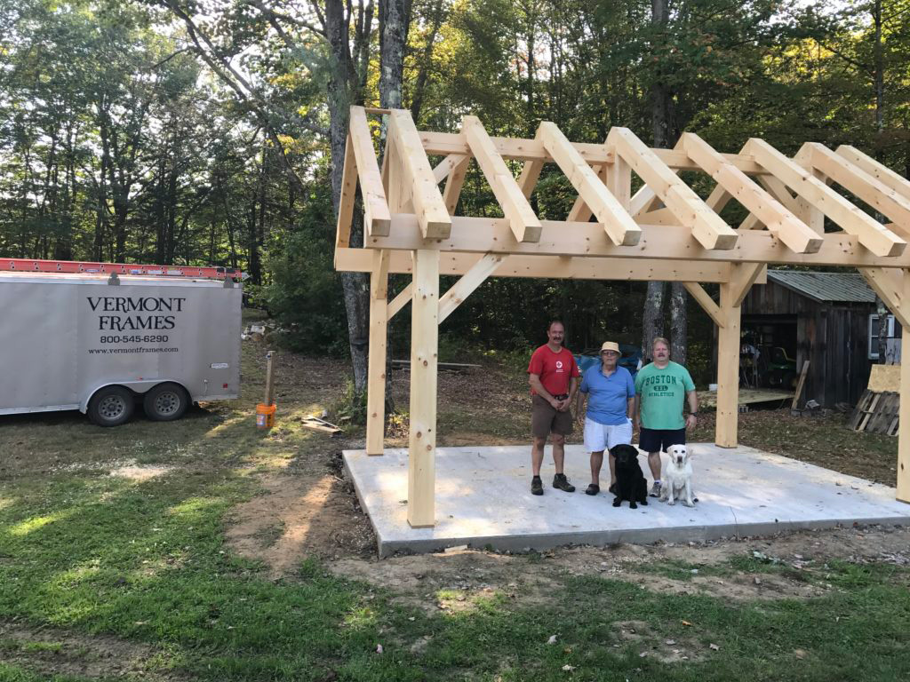 Timber frame pavilion structure with 3 people and 2 dogs