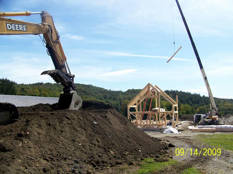Backhoe and crane being used to build a timber frame restaurant