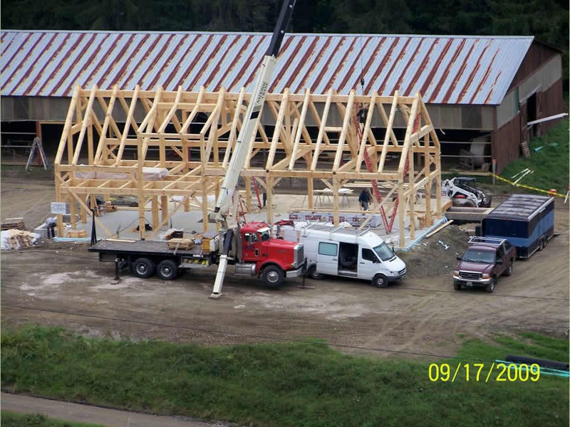 Crane assembling the timber frame structure of a restaurant