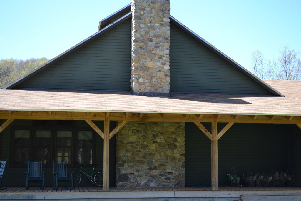 Finished exterior of a timber frame summer camp mess hall with a large stone chimney