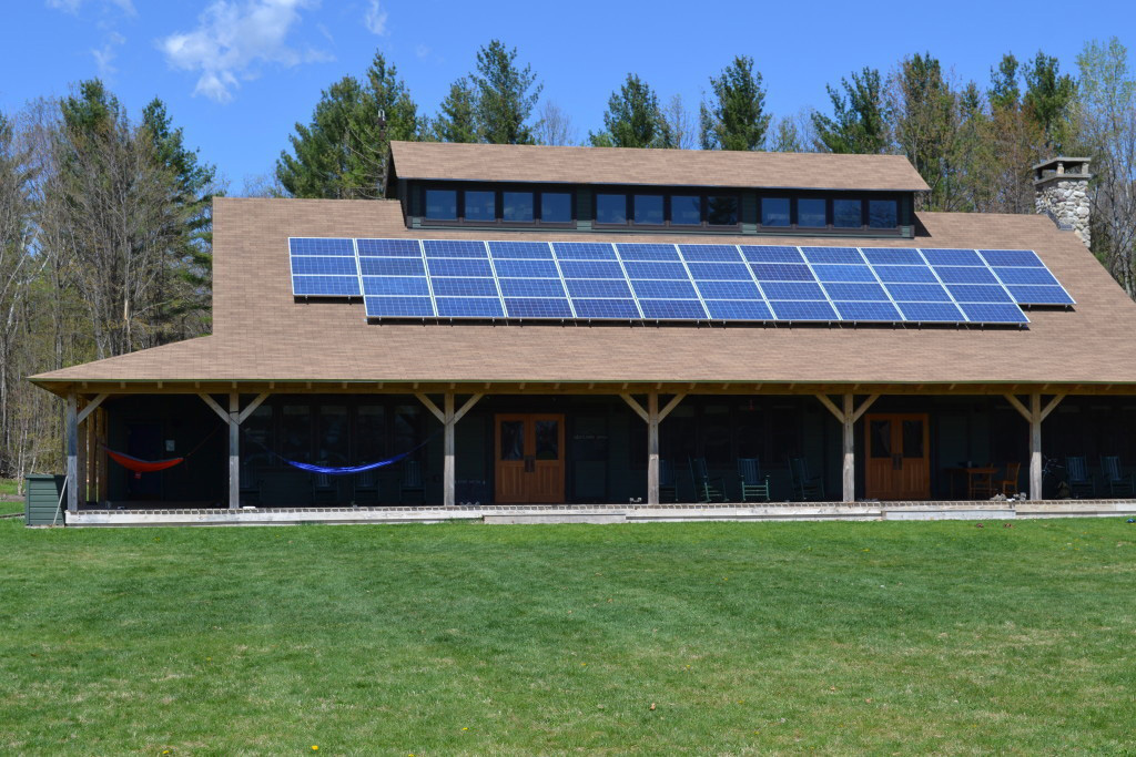 Finished exterior of a timber frame summer camp mess hall with solar panels on the roof