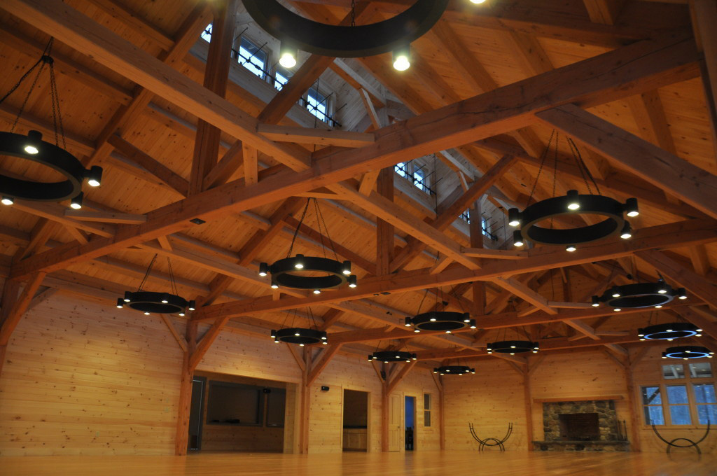 Timber frame ceiling in a summer camp mess hall with circular lighting
