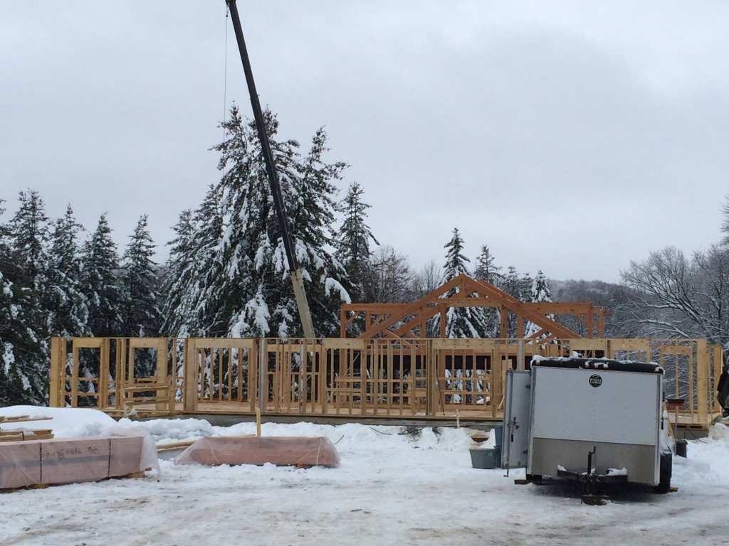 Timber frame structure of a summer camp pavilion with a crane