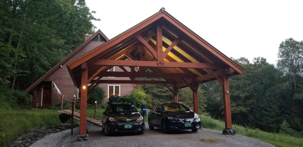 Finished timber frame car port with two vehicles underneath.