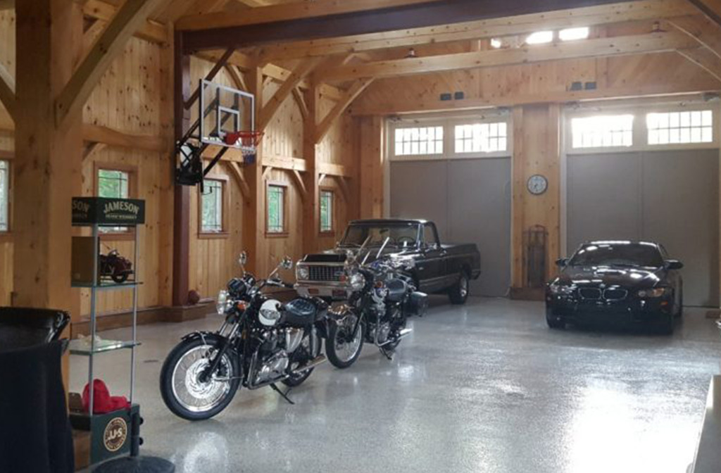 Finished timber frame barn interior with cars and motorcycles