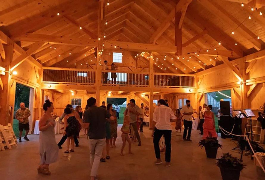 Interior of a finished barn with people dancing