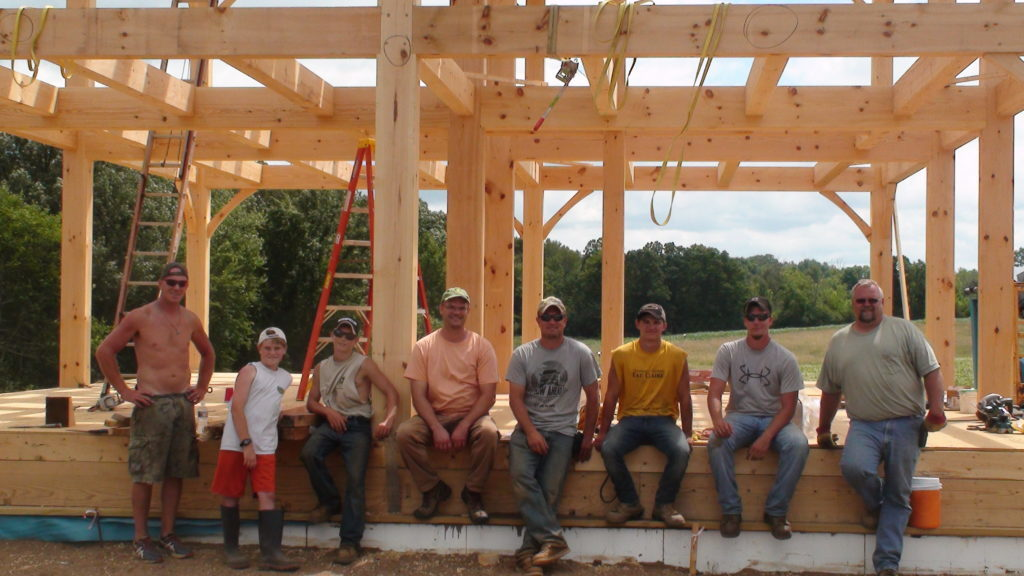 Crew sitting in front of timber frame structure