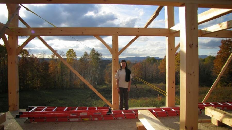 Girl standing in front of timber frame structure