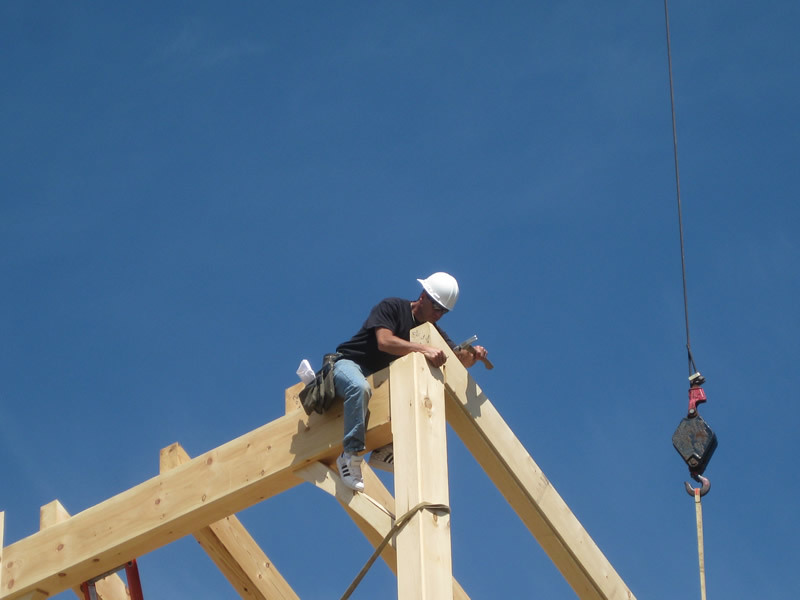 Man on timber frame colonial structure