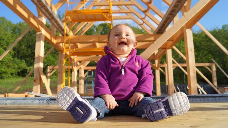 Baby sitting in front of a timber frame structure