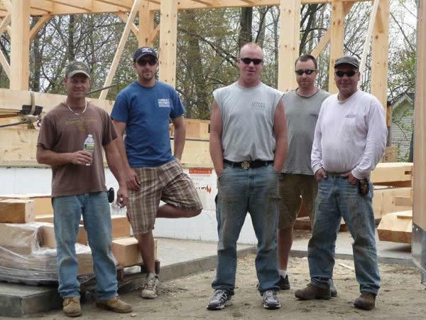 Crew in front of timber frame colonial structure